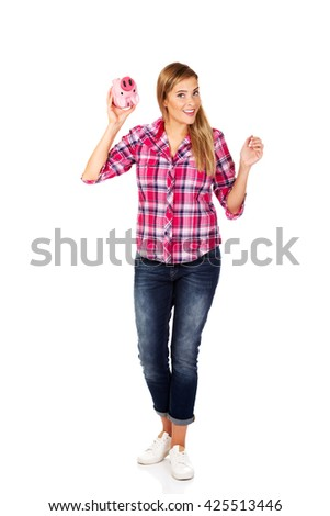 Young smiling woman holding piggybank  - stock photo