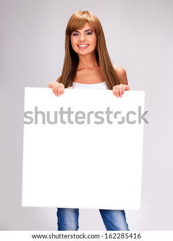 Young smiling woman holds white big banner posing at studio