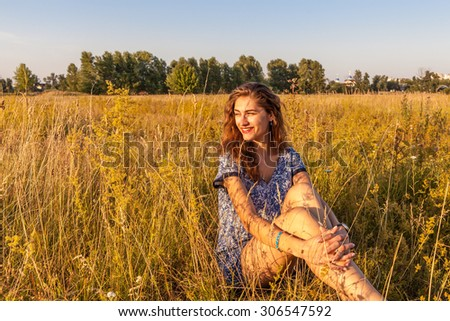 Young smiling woman in a blue dress is sitting in the field among the herbs