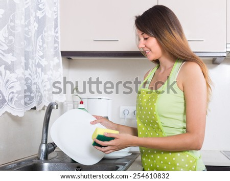 Young smiling woman in apron washing kitchenware in the kitchen
