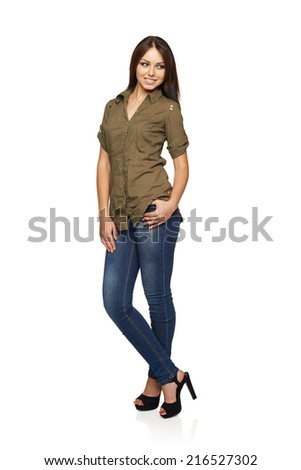 Young smiling woman in jeans and green shirt standing relaxed in full length looking to the side, over white studio background - stock photo