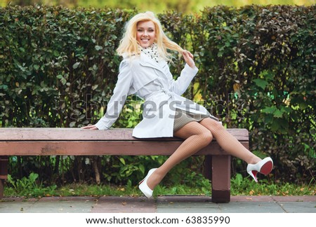 Young smiling woman in park sitting on bench. - stock photo
