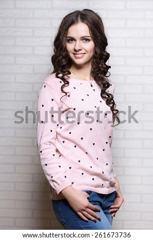 Young smiling woman in pink blouse posing near the wall - stock photo