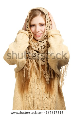 Young smiling woman in warm comforter and knitted sweater standing isolated on white background - stock photo
