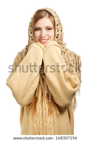 Young smiling woman in warm sweater and knitted comforter standing isolated on white background - stock photo