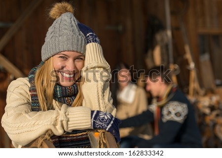 Young smiling woman in winter clothes cottage enjoy holiday friends - stock photo