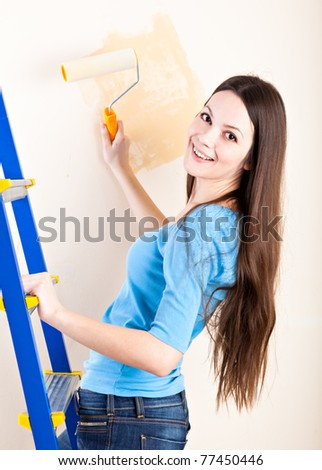 Young smiling woman is painting walls