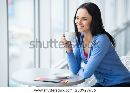 Young, smiling woman is sitting in the airport with coffee while waiting for flight. - stock photo