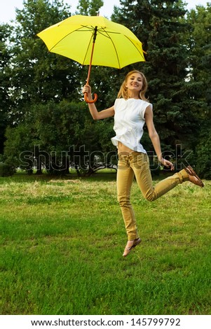 Young smiling woman jumping with yellow umbrella in a park