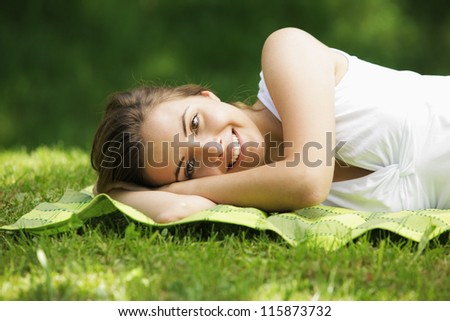 Young smiling woman laying on the grass