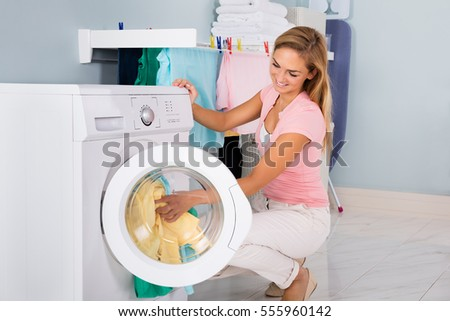 Young Smiling Woman Loading Untidy Clothes In Washing Machine In Utility Room