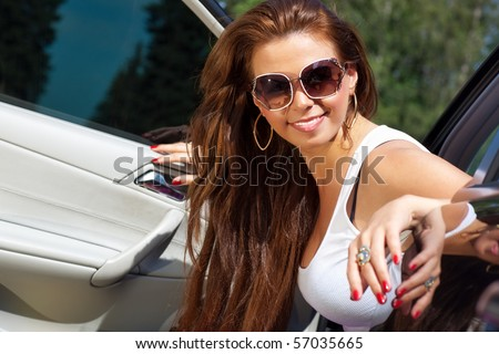 Young smiling woman looking out of her car. - stock photo