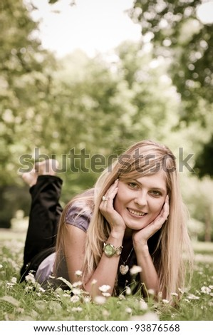 Young smiling woman lying in grass during sunny day (park - outdoors) - stock photo