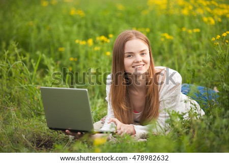 Young smiling woman lying on the grass with notebook in park looking to camera