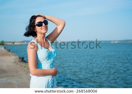 Young smiling woman on quay - stock photo
