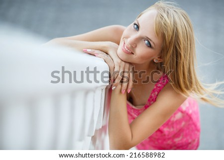 Young smiling woman outdoors portrait. Soft sunny colors.Close portrait. Summer portrait of a beautiful young blonde Caucasian girl with straight hair in blue dress outdoors in the city - stock photo