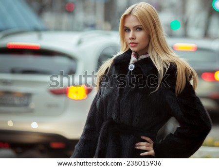 Young smiling woman outdoors portrait. Soft sunny colors.Close portrait. winter portrait of a beautiful young blonde Caucasian girl with straight hair in blue dress outdoors in the city  - stock photo