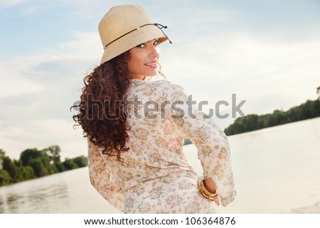 young smiling woman portrait with hat at lake summer day - stock photo