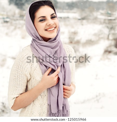 Young smiling woman posing on the snowy field - stock photo