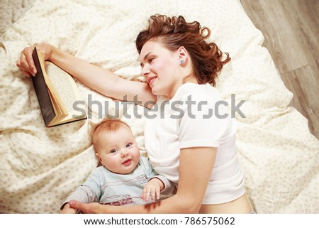 young smiling woman reading a book while lying on bed with baby