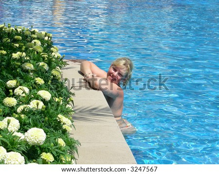 young, smiling woman relaxing in the sunny pool at resort - stock photo