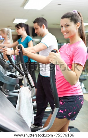 young smiling woman running on the treadmill with other people on background - stock photo