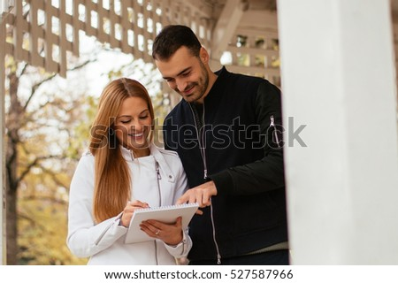 Young smiling woman showing notes to handsome man.