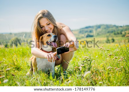 Young smiling woman showing something to her dog on smart-phone, outdoor in nature - stock photo