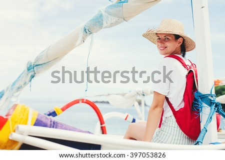 Young smiling woman sitting at sailboat on beautiful island at sunny day