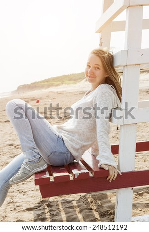 Young smiling woman sitting on lifeguard chair at Atlantic beach in Prince Edward Island, Canada. - stock photo
