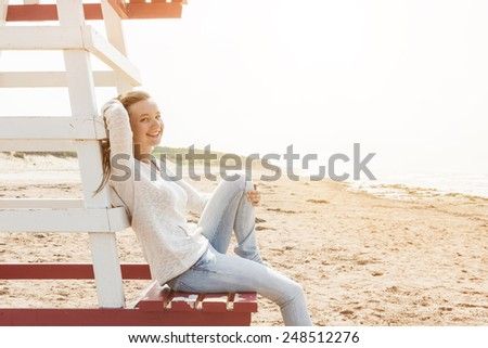 Young smiling woman sitting on lifeguard chair at Atlantic beach in Prince Edward Island, Canada, with copy space. - stock photo