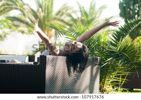 Young smiling woman sitting on the chair - stock photo