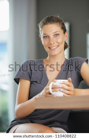 Young smiling woman sitting with a cup of coffee - stock photo