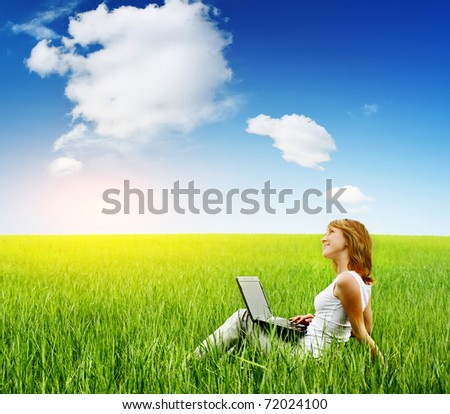 Young smiling woman sitting with laptop on green grass and looking to a sky.