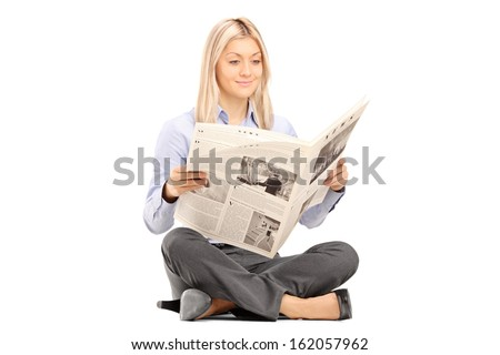 Young smiling woman sittong on a floor and reading a newspaper isolated on white background