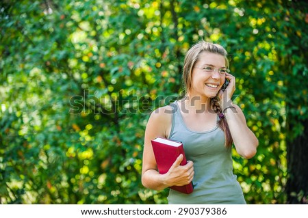 Young smiling woman speaks by mobile phone? with red book.