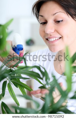 Young smiling woman spraying flowers, close up - stock photo