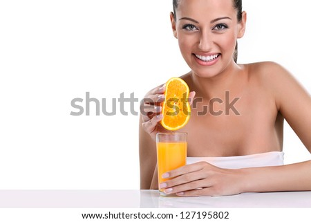 young smiling woman squeezes orange juice into a glass - stock photo