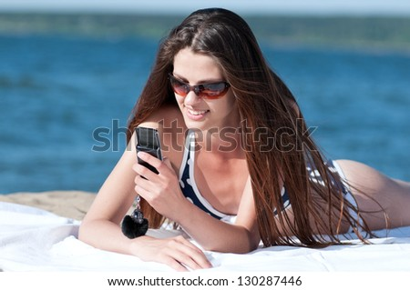 Young smiling woman talking by phone on a beach - stock photo
