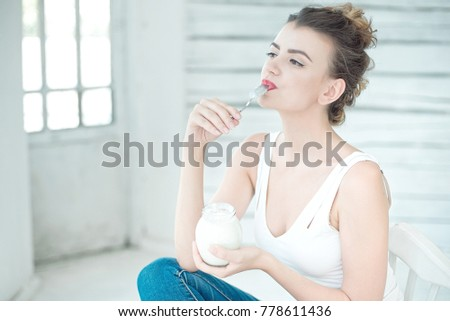Young smiling Woman Tasting Fresh Organic Yogurt sitting in white bright room, wearing in white singlet. Healthy Lifestyle Concept.