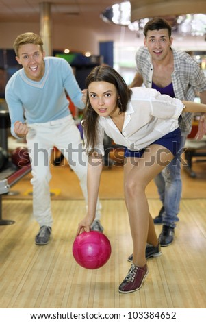 Young smiling woman throws ball in bowling; tow men support her; shallow depth of field - stock photo
