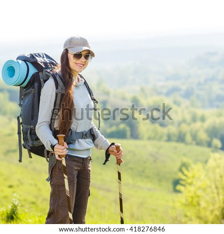 Young smiling woman traveling with backpack on grassy hills. Cheerful caucasian girl in sunglasses enjoying summer holidays - stock photo
