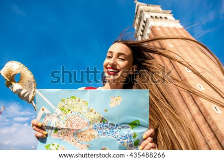 Young smiling woman traveling with carnaval mask and paper map on San Marco square in Venice. - stock photo