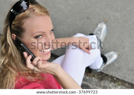 Young smiling woman wearing rollerblades calling with mobile phone outdoors