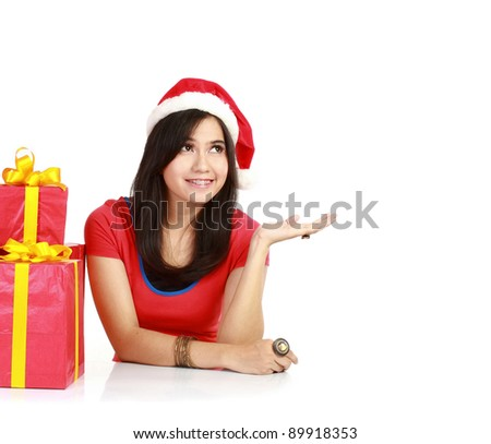 Young smiling woman  wearing Santa Claus hat presenting something in isolated white background - stock photo