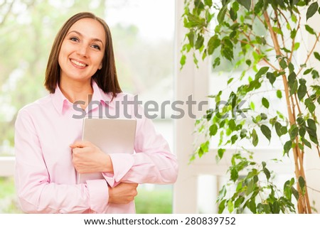 Young smiling woman with a pink shirt standing with a tablet pc in her hands - stock photo