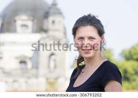 Young smiling woman with blurry church in a background