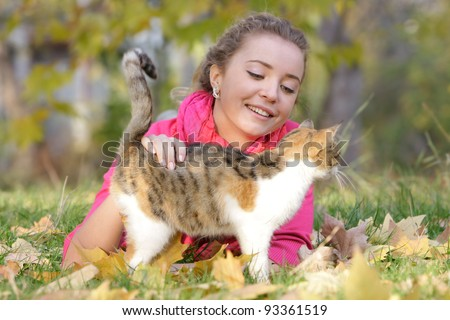 young smiling woman with cat outdoors - stock photo