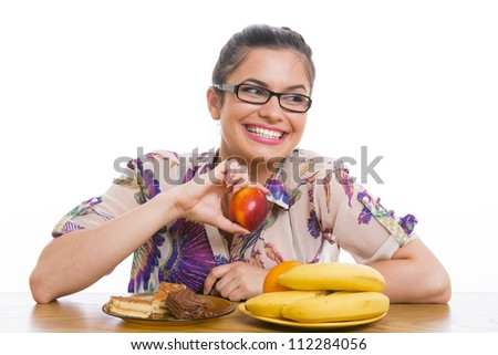 Young smiling woman with fruits and cakes, holding nectarine, over white background. Dieting concept. - stock photo