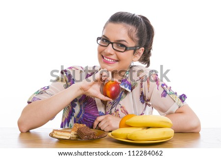 Young smiling woman with fruits and cakes, over white background. Dieting concept. - stock photo